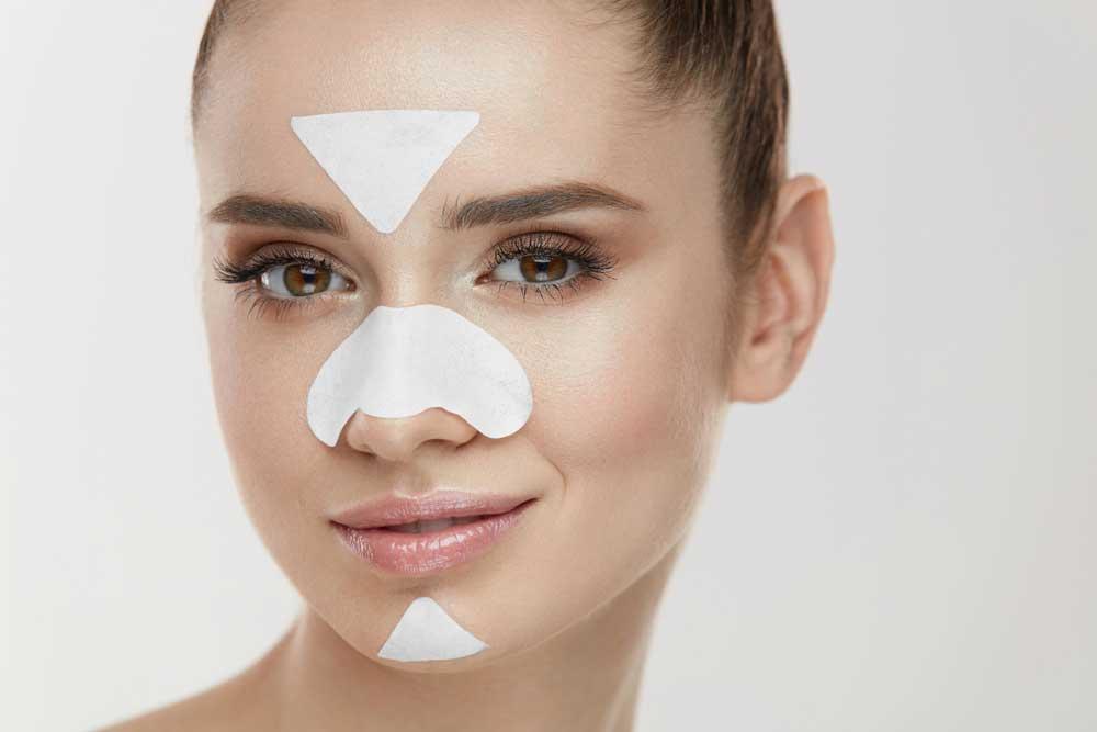 donna con cerotti per rimuovere i punti neri su fronte naso mento