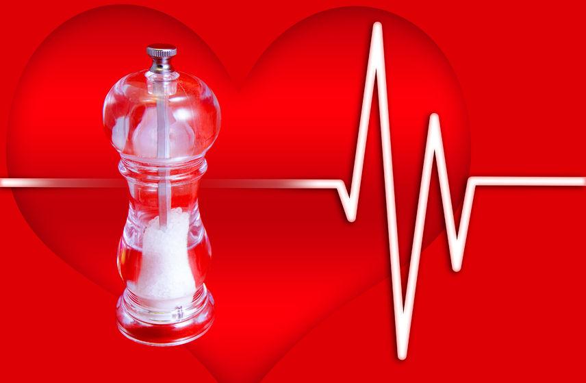 nella foto una saliera su sfondo rosso con un cuore e elettro-cardiogramma