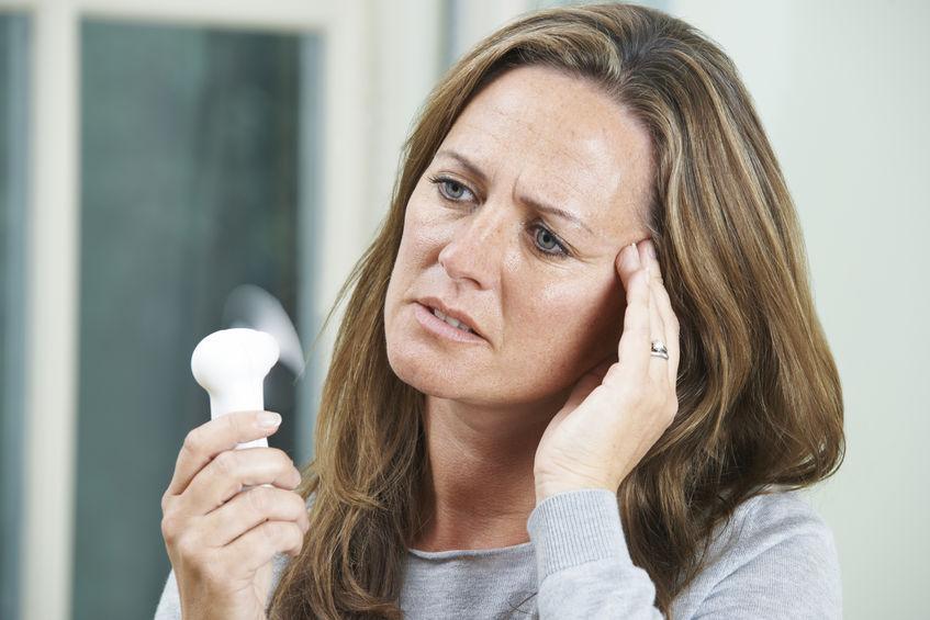 donna che affronta le vampate di calore con un mini ventilatore