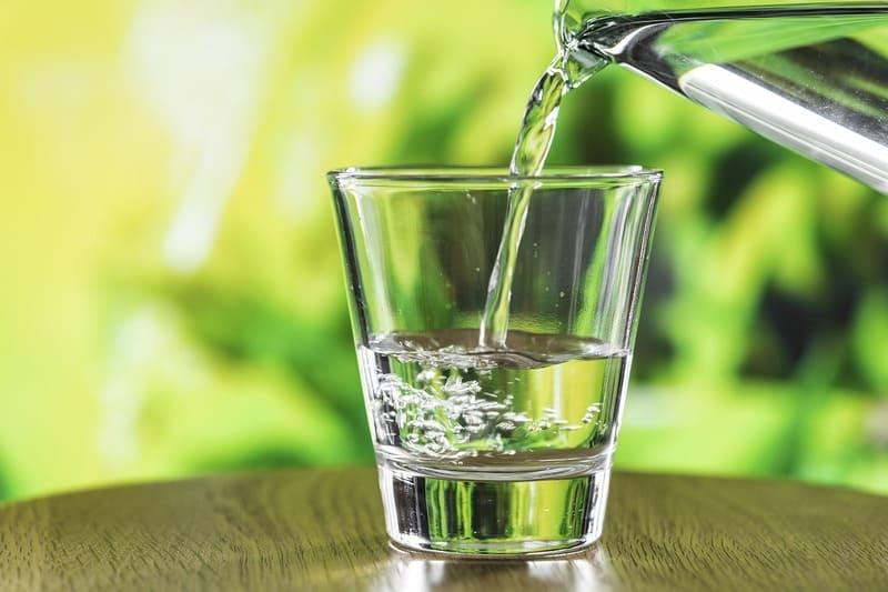 Foto di una brocca dalla quale fuoriesce acqua che cade in un bicchiere